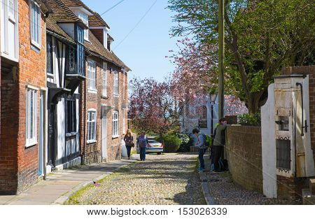RYE, UK - 1 MAY, 2016: Old street of Rye town with periodic buildings. Mermaid Street showing typically steep slope and cobbled surface