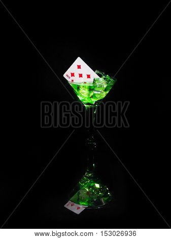 Playing card in a cocktail glass on black background. casino series.