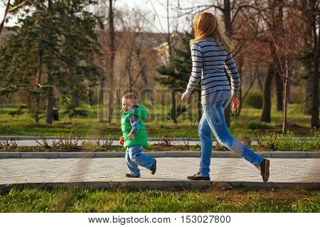 Mom catches her son in the autumn park. Family time. Happiness of childhood and parenthood. Outdoor Activities.