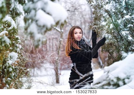 Cute attractive girl in a fur coat and gloves in the winter park. Winter fun. Walks in the open air.