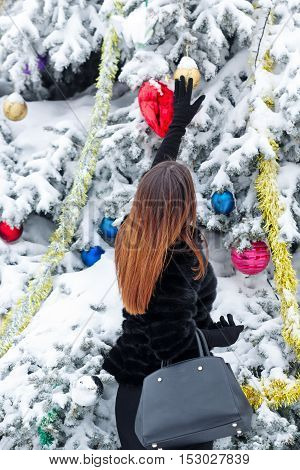 Portrait of pretty attractive girl in fur coat and gloves in the winter park. She decorates the Christmas tree toys. Winter fun. Walks in the open air.