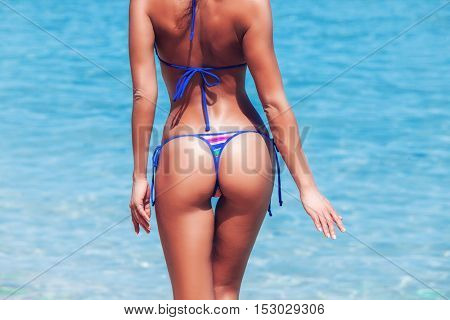 Woman in bikini on blue sea background, close up photo of hips