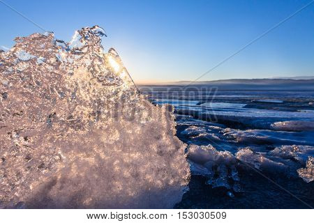 Sun At Sunset Shining Through The Transparent Texture Of The Ice Floe In Lake Baikal
