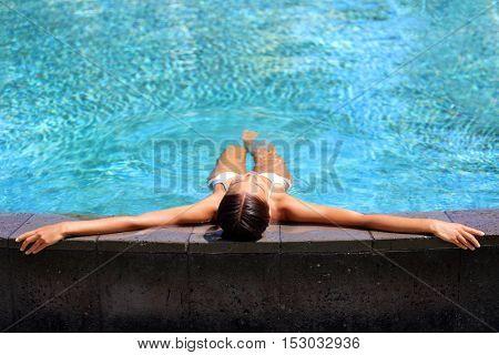 Bikini woman lying relaxing in infinity pool at luxury resort spa retreat. Beautiful unrecognizable woman sunbathing in swimsuit on the edge of pool enjoying the blue water. Getaway vacation