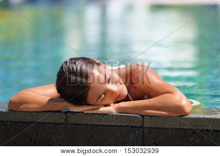 Woman relaxing sunbathing in infinity swimming pool at health spa retreat. Luxurious body care pampering Serene Asian young lady enjoying sun time at resort hotel facilities. Tranquility and comfort.