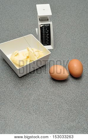 A scale butter and eggs on a worktop in the kitchen