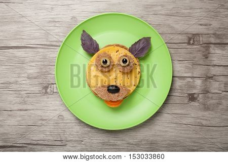 Funny dog made of bread and cheese on plate and wood