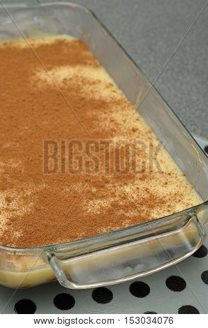 Milk tart in a glass container on a grey background