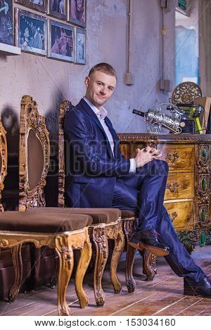 Full body picture of a young elegant business man sitting on a chair while putting his hands on his folded legs