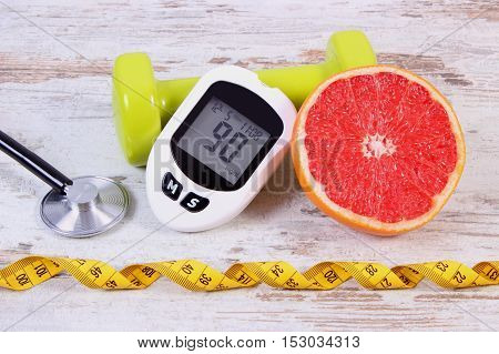 Glucose meter with result measurement sugar level medical stethoscope fresh grapefruit and green dumbbells for fitness concept of diabetes slimming healthy lifestyles and nutrition