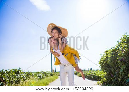 Multi ethnic inter racial couple lovingly having a piggy back ride in the countryside
