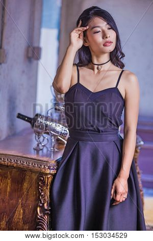 Beautiful elegant Chinese girl in stunning dress looking away from camera as she prepares to get ready before going out for dinner with her husband
