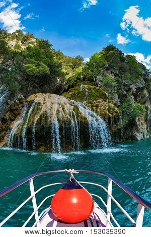 Pleasure boat with the red lantern. Travel to Provence. Waterfall in the river Verdon