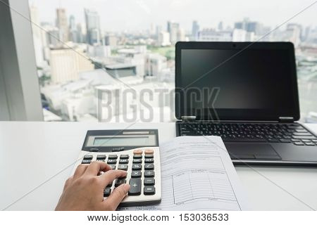 businesswoman use calculator with laptop for paperwork