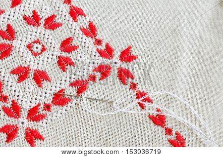 Embroidered fragment on flax by red and white cotton threads. Macro embroidery texture flat stitch. Geometric ornament.