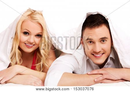 Happy couple lying under blanket looking at camera