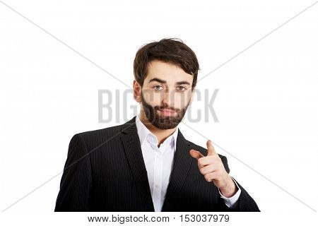 Happy businessman points his finger on you.
