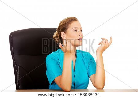 Female doctor sitting behind the desk and talking with someone