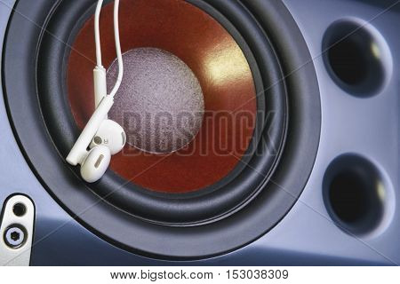 earphone on the background of musical speaker. The musical equipment. Close up
