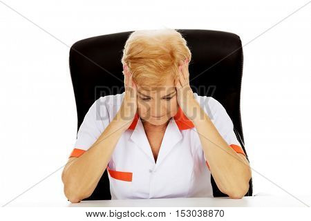 Elderly female doctor or nurse sitting behind the desk with headache