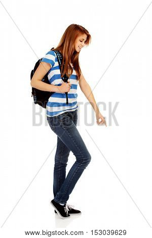 Teenager woman with backpack pointing for soomething