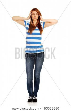 Teenage woman with headache holding her hand to the head