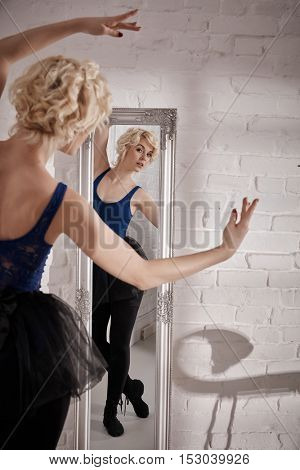 Ballet dancer practicing, looking at herself in mirror.