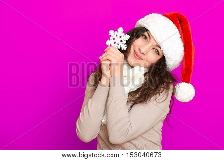 girl in santa hat portrait with big snowflake toy posing on pink color background, christmas holiday concept, happy and emotions