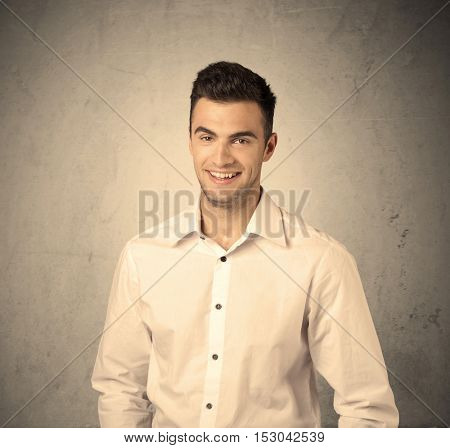 A young handsome business person making facial expression in front of clear, empty concrete wall background concept