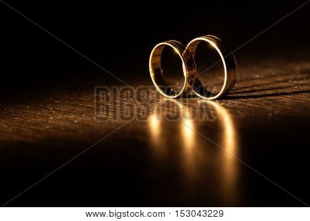Wedding rings in rays of light with a beautiful shadow.