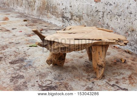 Wooden table made from tree in the old brick wall background.