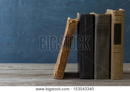 Stack of old books on a wooden bookshelf close up