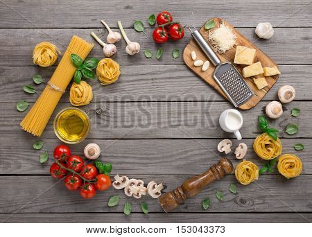 Fettuccine and spaghetti with ingredients for cooking pasta on wooden background top view