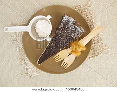 Cheesecake with chocolate icing and powdered sugar