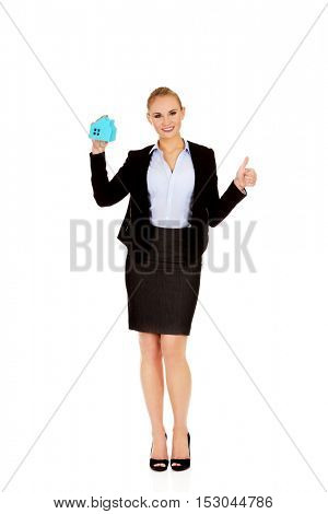 Smile business woman holding a paper house and show thumb up