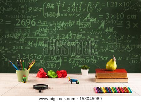 A stuffed school desk with green blackboard in the background full of numbers, calculation