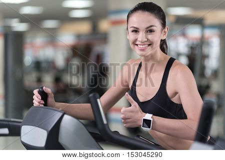 I like it. Happy young pretty woman training in a gym and making an approving gesture with her thumb up while running on a treadmill.