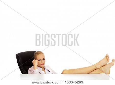 Tired young business woman holding legs on the desk