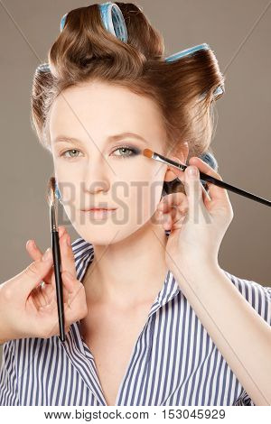 Young woman in curler in her hair and one eye with make-up. With multiple hands applying make up.