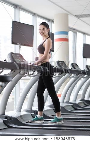 Do it faster. Active smiling young girl using a treadmill and doing exercises while training in a gym.g girl using treadmill in a gym