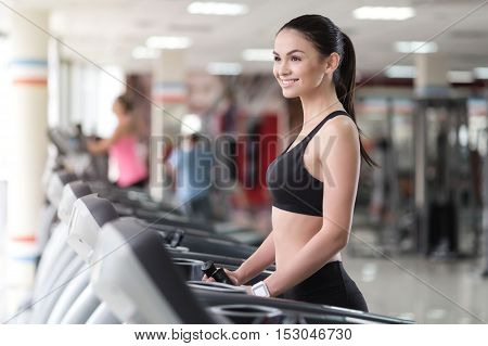 Finding harmony. Smiling young pretty woman spending time in a gym and using treadmill while having training.