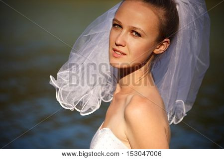 Sensual bride is standing near water outdoors