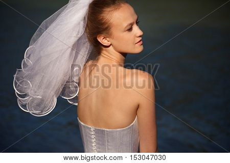 Stunning classical brides profile  with veil outdoors
