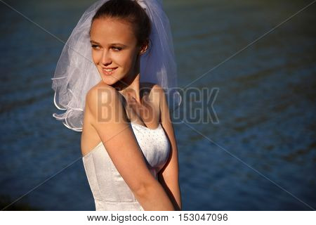 Young  beautiful bride  with veil near water outdoors