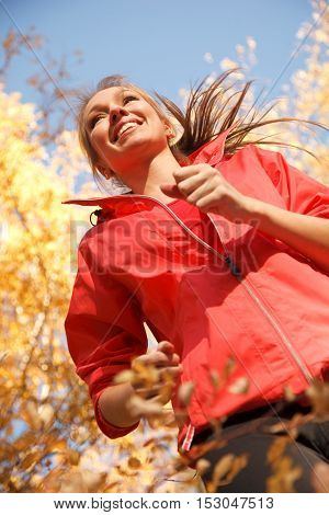 Jogging  young cheerful woman in autumn park