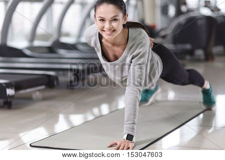 Never stop. Smiling delighted pretty girl doing exercises and improving her body while spending time in a gym.