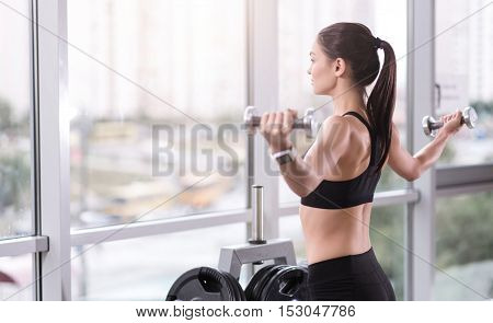 Be strong. Athletic young pretty girl training and using dumbbells while spending time in a gym.