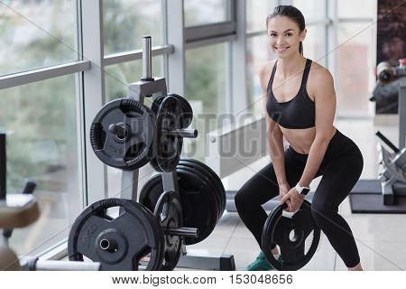 For a slim figure. Active beautiful young girl doing squatting exercises while having workout and enjoying time in a gym.