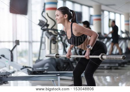 Young and powerful. Slim delighted pretty girl doing barbell squat while having workout training in a gym.