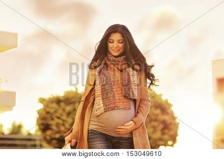 Beautiful pregnant woman with shopping bags outdoors, with pleasure expecting a baby and preparing, happy pregnancy time